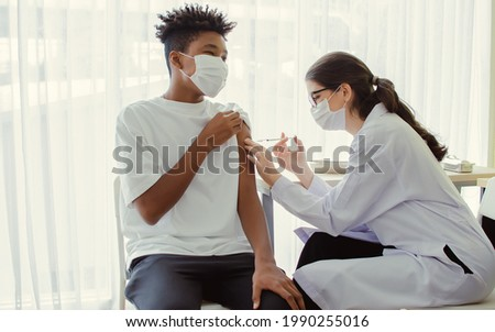 African teen man wearing face mask, getting vaccination to protect or prevent covid19 virus, getting scary vaccine injection while female caucasian doctor preparing syringe to vaccinate at hospital Foto stock ©