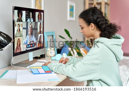 African teenager high school student remote learning online group class at home. Mixed race teen girl distance studying during virtual class, group online lesson on video conference call with teacher.