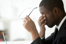 African tired businessman feels eyestrain taking off optical computer glasses, holding spectacles in hands massaging eyes, eyesight problem correction, fatigue, overwork and stress at work concept