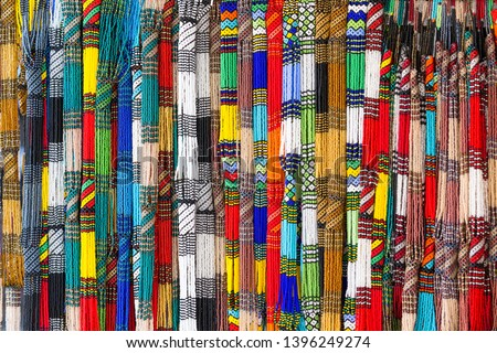 African traditional beadwork necklaces, bright, vibrant, colourful, handmade and hanging up at a street market on sale in Cape Town, South Africa suitable for use as background, abstract and wallpaper