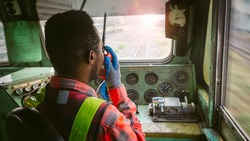 African train driver talking radio communication or walkie talkie in  interior room to control place of train