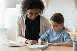 African tutor engaged with schoolgirl help complete tasks seated at table at home. Concept of education kid development, european child homeschooling writing homework with american stepmother concept