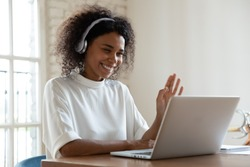 African tutor of language start on-line lesson with trainee wave hand smiling looks at pc screen. Mixed-race woman in headphones communicating distantly, e-learning process, application usage concept
