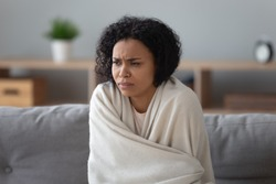 African unhappy woman sit on couch covered with plaid try to warming up in cold flat without central heating, system not working, girl feels unhealthy has common cold viral infectious disease concept