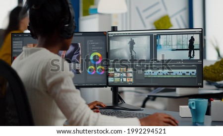 African video editor working with footage and sound, editing new project cutting film montage sitting in modern agency office. Woman using computer processing movie in post production software Сток-фото ©