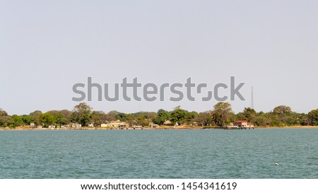 African village seen from the river. From this village. This is the birthplace from Kunta Kinte Stock fotó ©