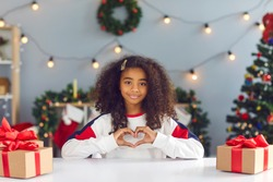 African vlogger girl doing a loving heart gesture while making video, thanking subscribers and followers for support, promoting charity on social media and wishing Merry Christmas and Happy New Year