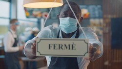 African waiter in safety mask turning ferme sign on french cafe glass door. Afro staff of restaurant turning open closed sign in french closing because of covid-19 epidemic