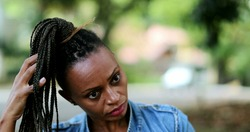 African woman adjusting dread hair outside