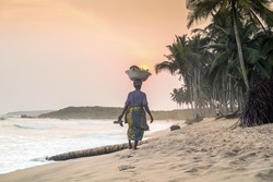 African woman at beautiful sunset on a paradise beach, West Africa