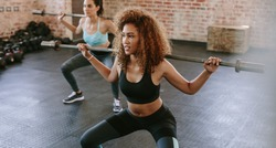African woman exercising with barbell in fitness class. Female workout in gym with barbell.