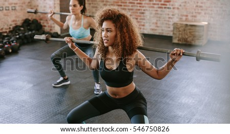 African woman exercising with barbell in fitness class. Female workout in gym with barbell. #546750826