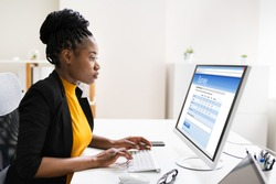 African Woman Filling Survey Poll Or Form On Desktop Computer