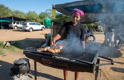 African woman grilling some chicken at her street food stall