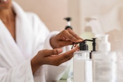 African woman hands using cosmetic liquid soap in bathroom. Close up of girl black hands in bath robe using body lotion dispenser after shower. Black girl putting pomade on hand from pump.