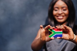 African woman hold small South Africa flag in hands.