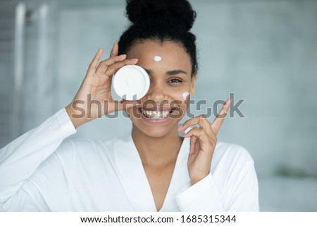 African woman in bathrobe applied cream on face holds jar feels happy looks at camera, anti-wrinkle treatment, remedy for complexion improvement, deep repair, facial skin protection, skincare concept