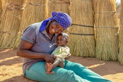 African woman in the village holding her child in the lap,