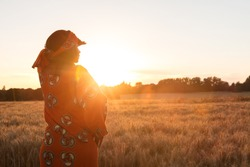 African woman in traditional clothes standing, looking, hand to eyes, in field of barley or wheat crops at sunset or sunrise