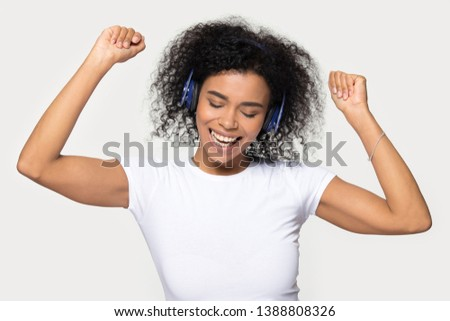 African woman in white t-shirt and headphones moving dancing listens favourite track modern music feels overjoyed having fun mood girl enjoy good audio sound amuse with eyes closed studio shot on grey