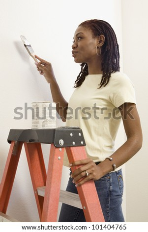 African woman on ladder painting