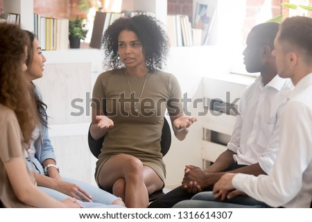 African woman psychologist coach speaking at diverse team training or group therapy session, black female trainer counseling addicted people or employees talking sharing problems sitting in circle #1316614307