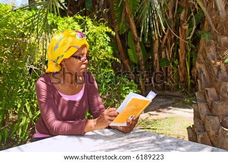 African woman reads book in shadow of a palm. Shot in the Botanical Garden, Stellenbosch, Western Cape, South Africa.