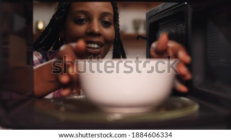 African woman reheat food in ceramic bowl using microwave oven. View inside microwave of meal in dish spinning and warming for afro-american female