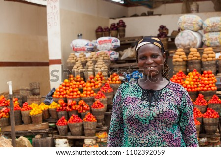African woman selling fresh fruits and vegetables at the farmers market