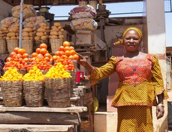 African woman selling fresh fruits and vegetables in the market
