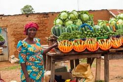African woman selling fruits and vegetables at the farmers market