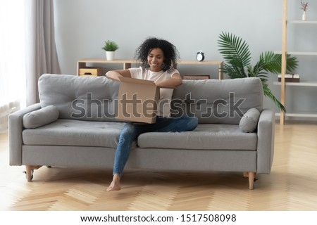 African woman sitting on couch in living room hold on lap big carton box unpacking received parcel feels happy, ordered online goods quick shipped at home, transport and delivery services ad concept