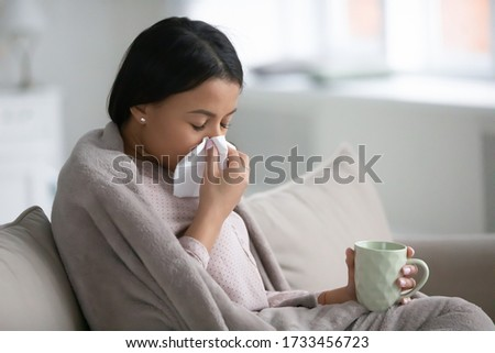 African woman sitting on sofa in living room wrapped in warm plaid hold paper handkerchief blow runny nose relief nasal stuffiness drinks cold medicine. Influenza flu symptoms, seasonal grippe concept Stock photo ©