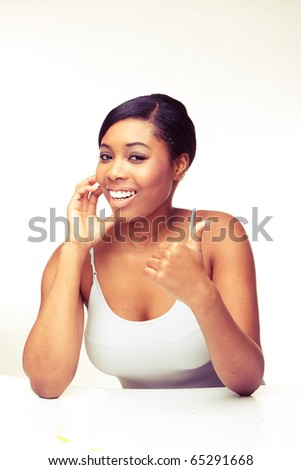 african woman speaking over the phone , looking on camera , showing thumb up