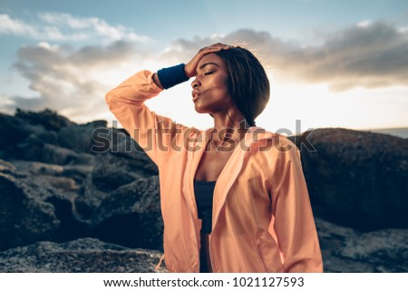 African woman standing with her hand on head after exhaustive workout. Fitness female feeling tired after intense workout.