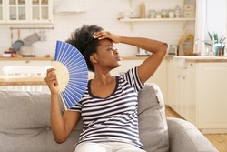 African woman suffer from heatstroke at home use paper fan for fresh air. Overwhelmed black millennial female tired of hot temperature indoors summertime in pain and headache holding hand on forehead