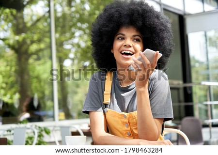 African woman user holding mobile phone in hand speak on speakerphone using virtual digital voice recognition assistant search on smartphone record audio message, ai tech app sitting in outdoor cafe.