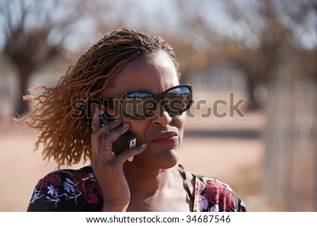African woman using her phone in the street, park