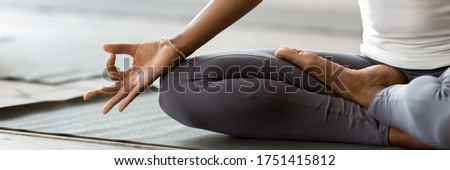 African woman wearing active wear do yoga practice meditating indoors, close up cropped photo lotus position. No stress, mindfulness, inner balance concept. Horizontal banner for website header design