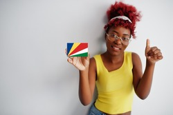 African woman with afro hair, wear yellow singlet and eyeglasses, hold Seychelles flag isolated on white background, show thumb up.