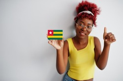 African woman with afro hair, wear yellow singlet and eyeglasses, hold Togo flag isolated on white background, show thumb up.