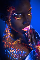african woman with body art glowing in ultraviolet light. Portrait of beautiful woman painted in fluorescent powder. isolated dark space