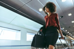 African woman with curly hairstyle traveling by plane. Female passenger walking through airport passageway towards flight boarding gate.