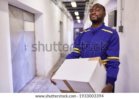 African worker as a temporary worker carries cardboard boxes through aisle to the warehouse of a shipping company Photo stock ©