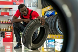 African worker doing inspection the tyre in car tyre service center concept of quality control product of retail business