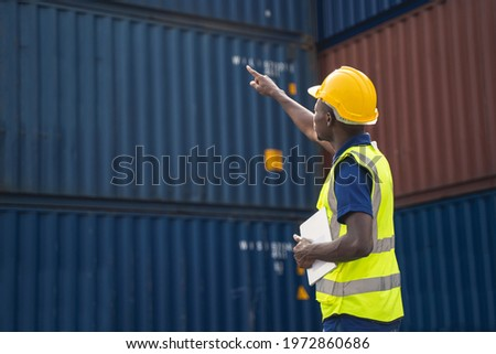 African worker holding a tablet, walking and checking the containers box from cargo ship for export and import Zdjęcia stock ©