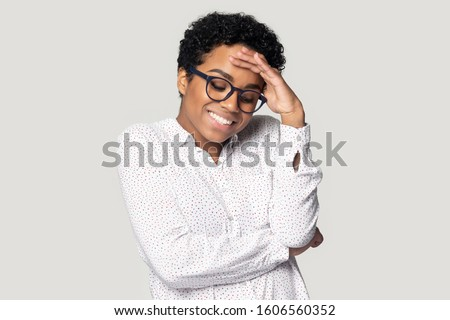 African young bespectacled woman in casual blouse posing indoors she lowers her eyes down and looks embarrassed feels very confused posing isolated on gray studio background, shy modest person concept