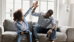 African young father and daughter play enjoy video games sit on couch, giving high five celebrating successful finish or start competition, activity with kids, fun concept