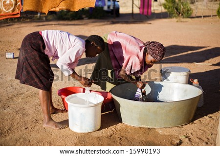 african young girl and an elderly woman washing clothes in the yard