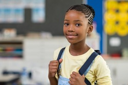 African young girl with blue backpack looking at camera. Pretty and satisfied black schoolgirl with rucksack smiling in class. Portrait of beautiful school girl standing in classroom.